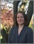 Image of Kathleen Gibson, one of PEATC's family support specialists. She is standing outside in front of a tree, smiling with her mouth closed. She has shoulder-length brown hair, and is wearing a grey sweater.