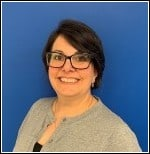 Image of Keri Peko, PEATC's business manager and military outreach coordinator. She is smiling and standing in front of a blue background. She has short black hair, black glasses, and is wearing a grey cardigan over a black shirt.