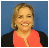 Image of Suzanne Bowers, the Executive Director of PEATC. She is smiling and standing in front of a blue background. She has short blonde hair, blue eyes, and is wearing a pink shirt under a black cardigan.