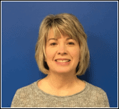 Image of Tammy Burns, PEATC's project manager. She is standing in front of a blue background, smiling. She has short blonde hair, bangs, and is wearing a tan shirt.
