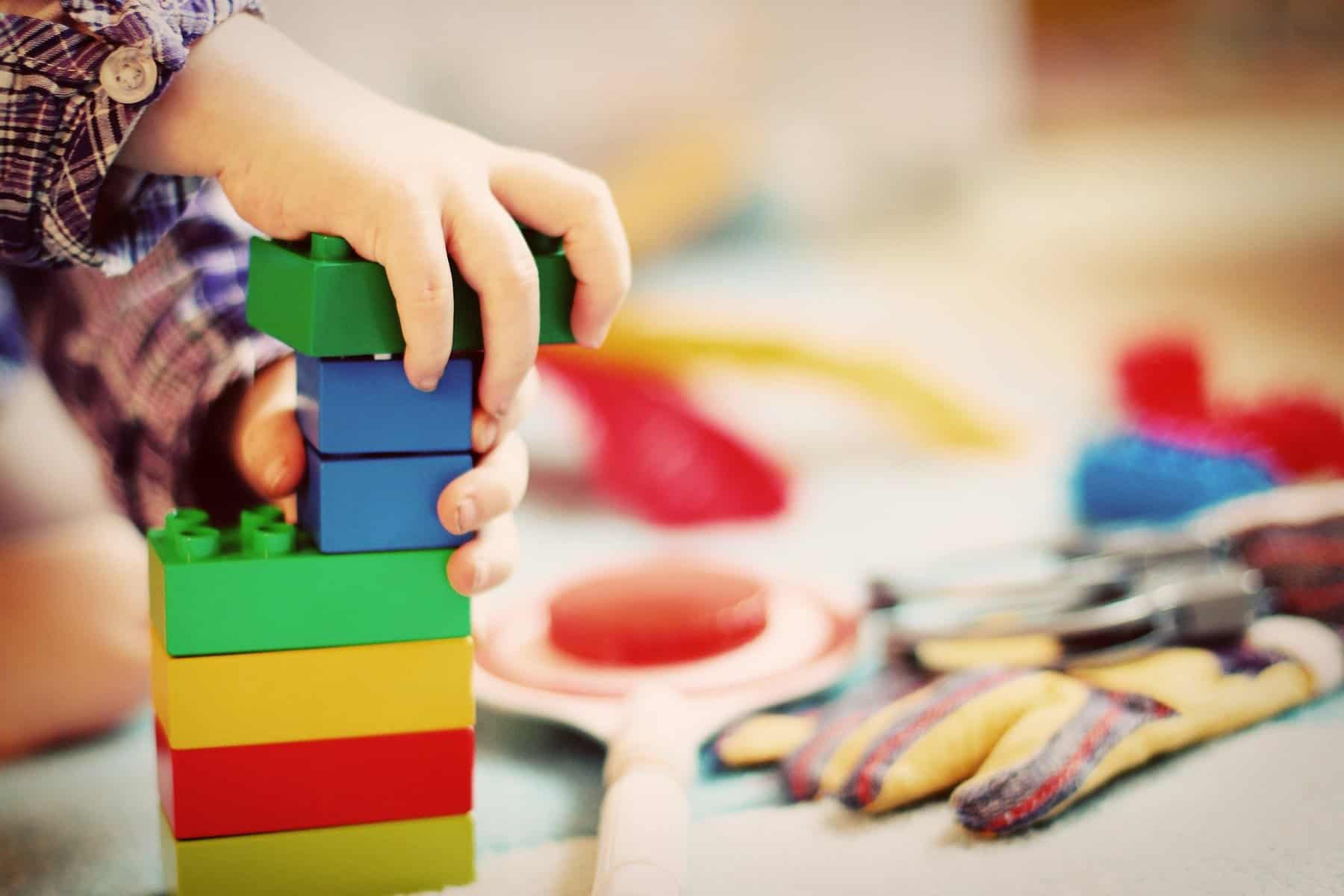 Colorful blocks stacked, child's hand in picture